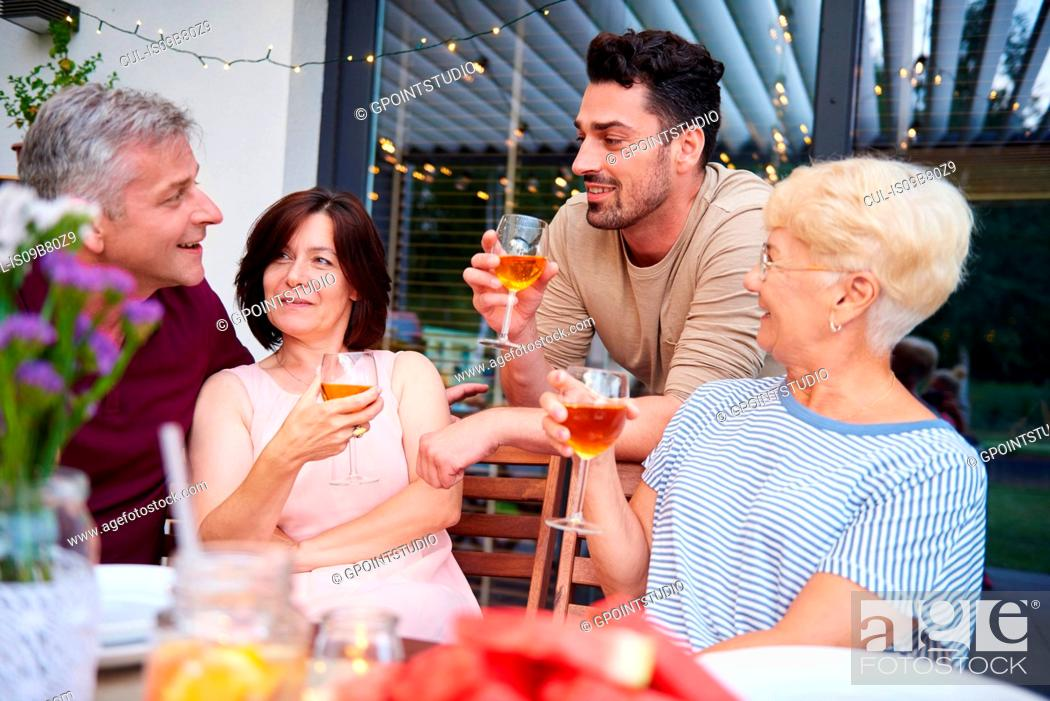 Imagen: Family adults talking and having wine with lunch on patio.