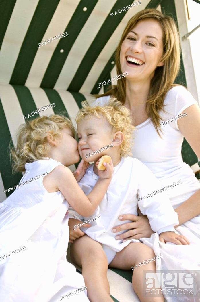 Stock Photo: Mother and 2 children on a swing chair.