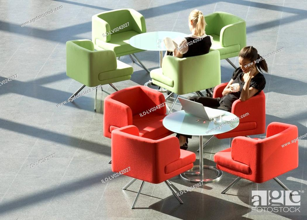 Stock Photo: Two businesswomen sitting at tables in an office building.