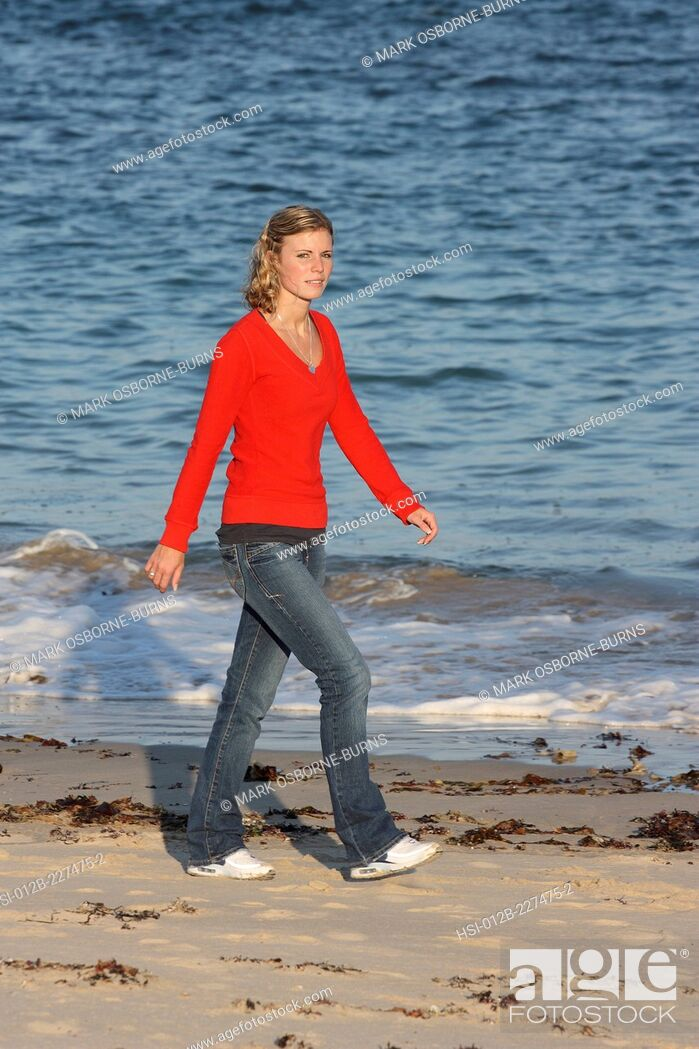 Stock Photo: Young blonde woman outdoors walking on the beach.