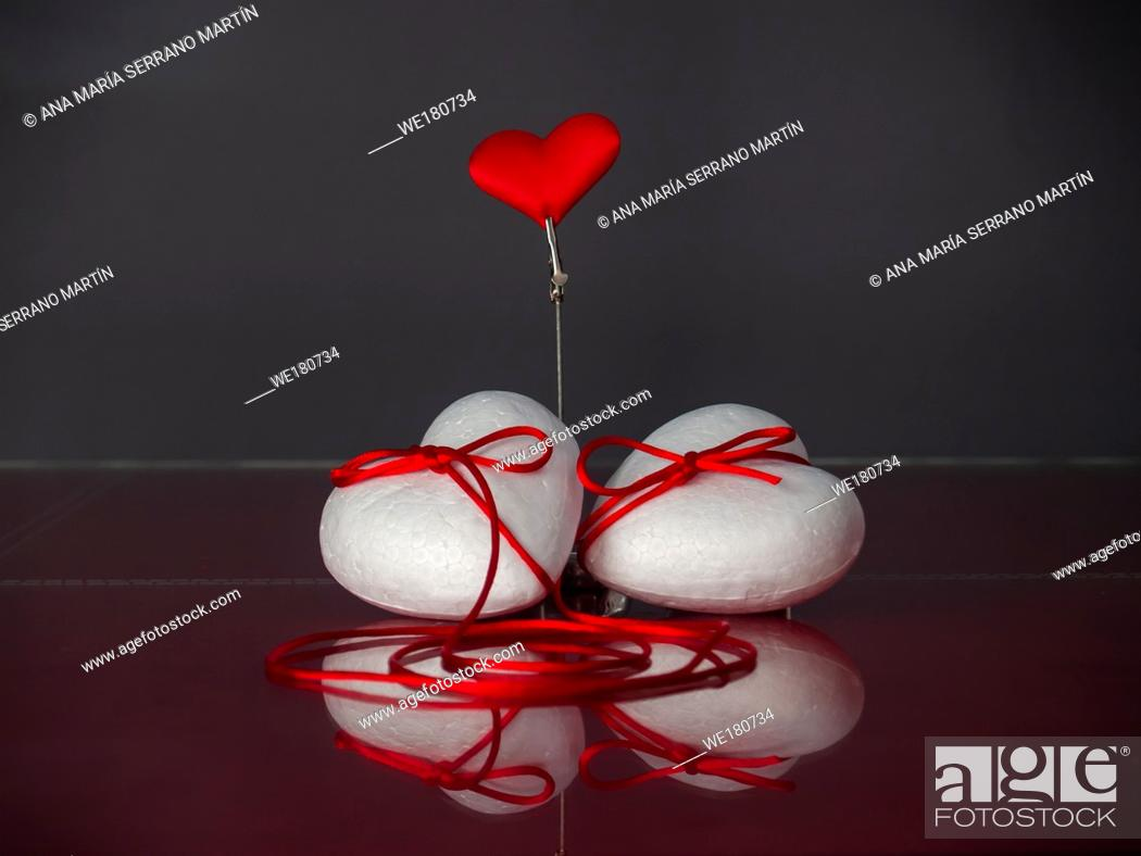 Stock Photo: Concept of love Two poliespan hearts joined with a red thread that symbolizes the legend of the red thread and one red heart.