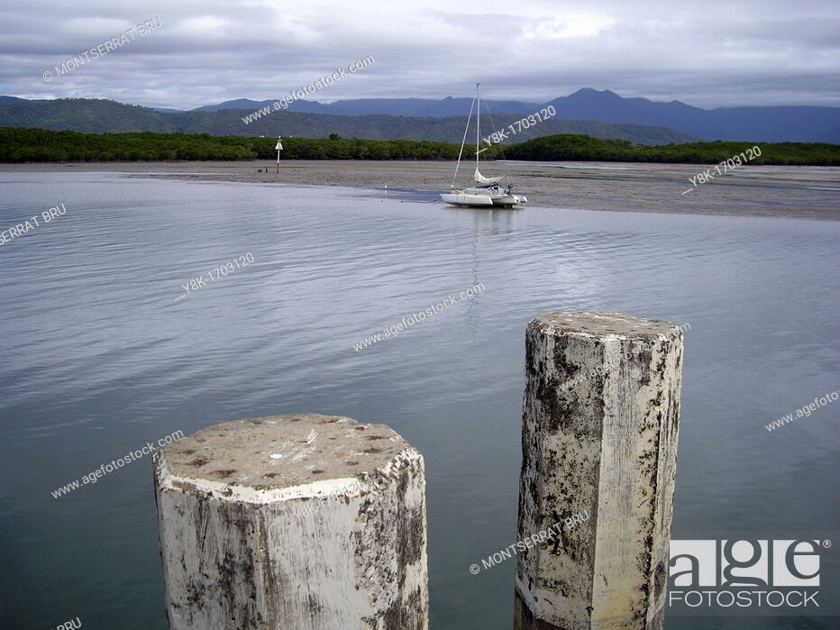 Stock Photo: Stranded catamaran during low tide in stormy weather inthe background and two berth poles in the foreground at Port Douglas, Queensland, Australia.