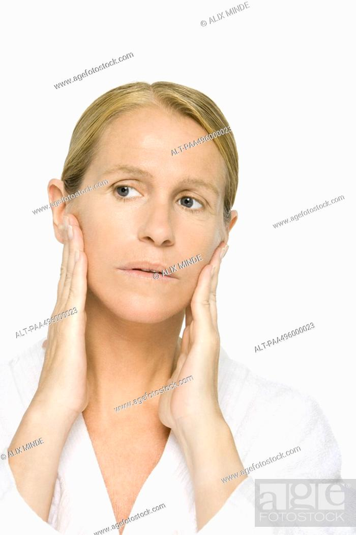 Stock Photo: Mature woman touching face, looking away.