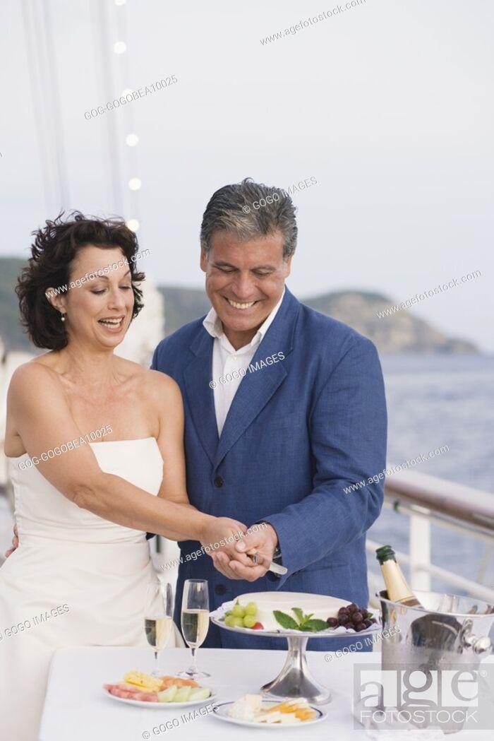 Stock Photo: Newlywed couple cutting wedding cake on boat deck.