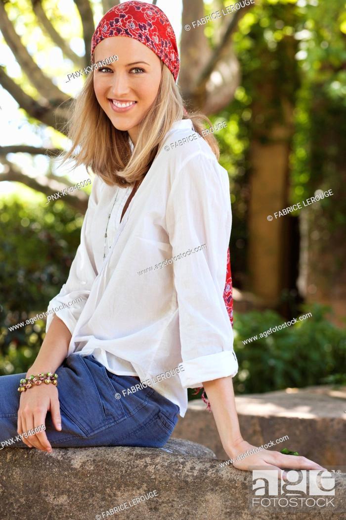 Stock Photo: Cheerful young woman wearing bandana.