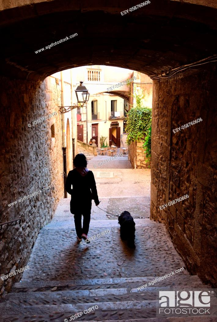 Photo de stock: tourist walking in the Arch in the street of Pujada de Sant Domenech, Agullana Palace in the background old town of Girona, Catalonia, Spain.
