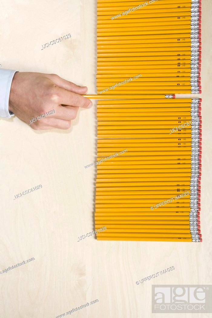 Stock Photo: Hand pulling pencil out of row.