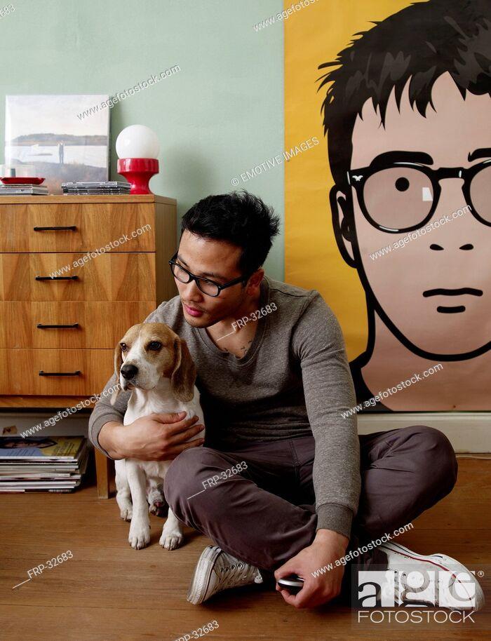 Stock Photo: Man caressing dog at home.