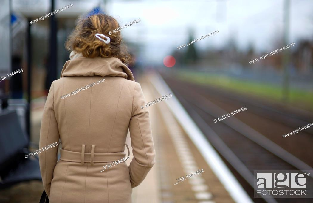 Stock Photo: Oisterwijk, Netherlands. Young woman in waiting for her commuter-train from Oisterwijk to Tilburg, Netherlands on the platform of this small railway-station.