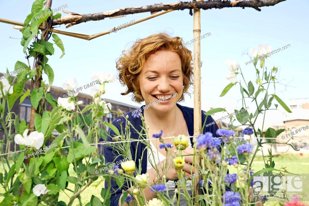 Stock Photo: Smiling young woman urban gardening.