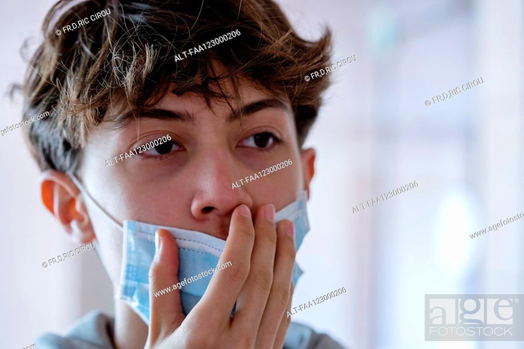 Imagen: Close up of teenage boy wearing blue surgical mask.