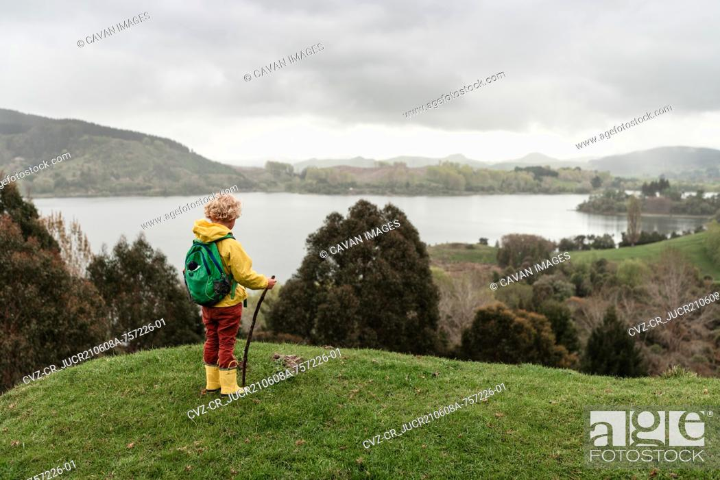Stock Photo: Child with backpack overlooking lake in New Zealand.