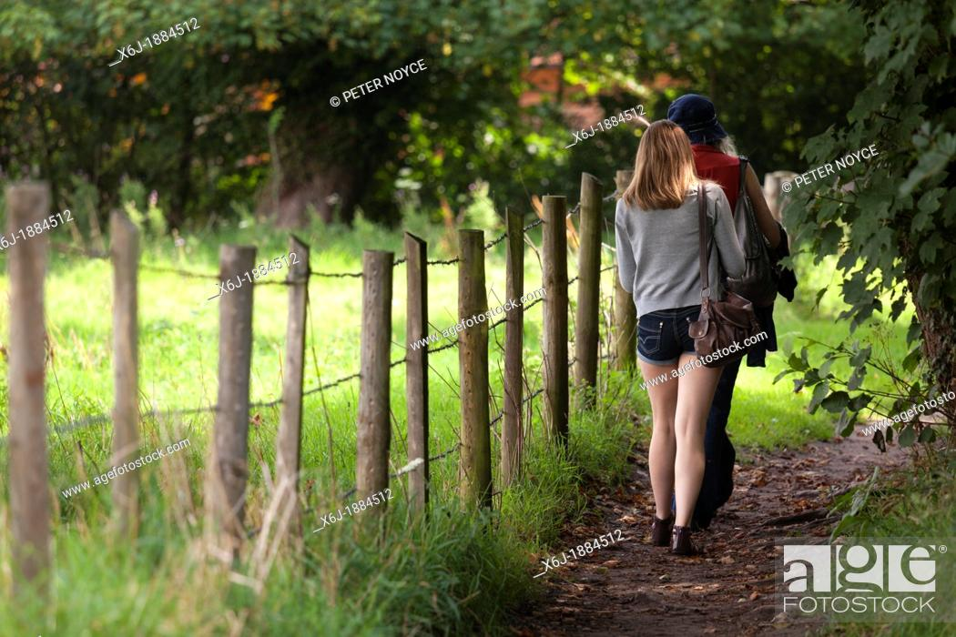 Stock Photo: back to camera girl and woman walking on country footpath alongside post and wire fence.