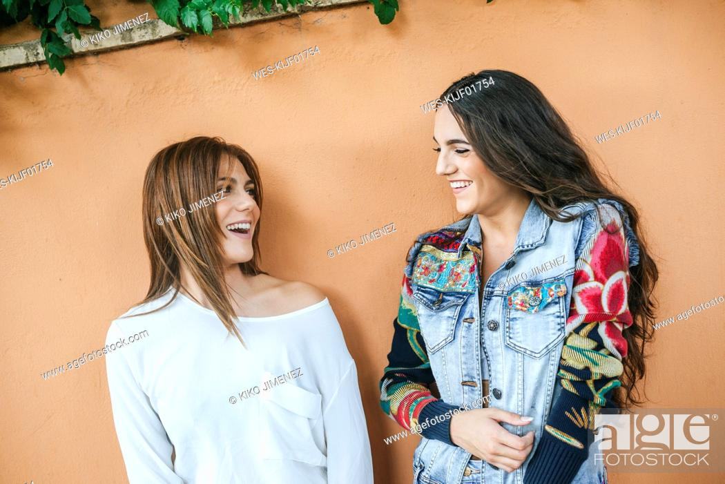 Stock Photo: Two laughing friends in front of wall.