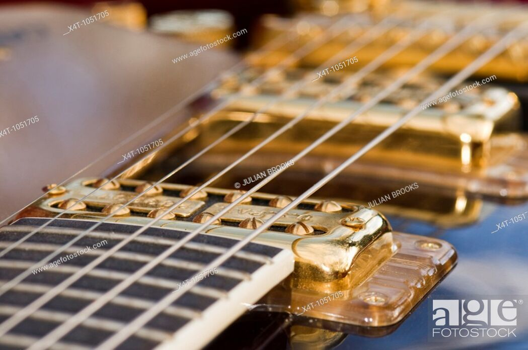 Stock Photo: The strings and pickups of a Gretsch guitar, detail with limited depth of focus.