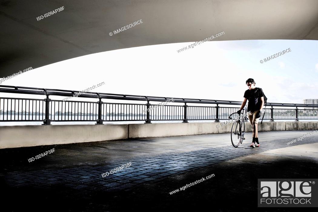 Stock Photo: Bike messenger walking, pushing bike.