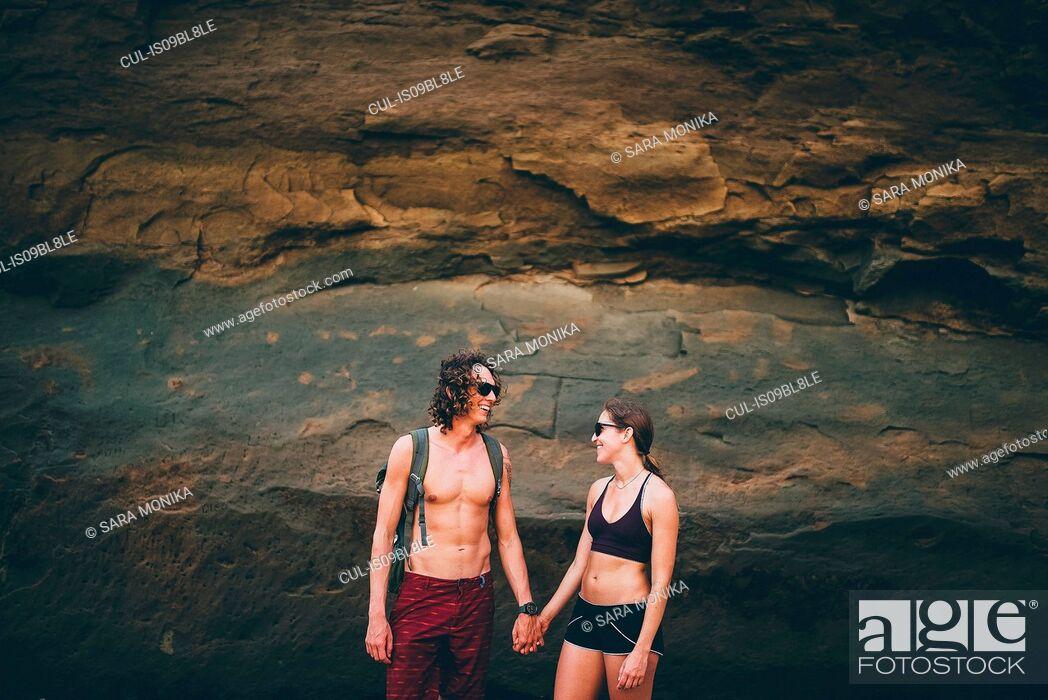 Stock Photo: Couple posing against rock face, Canoa, Manabi, Ecuador.