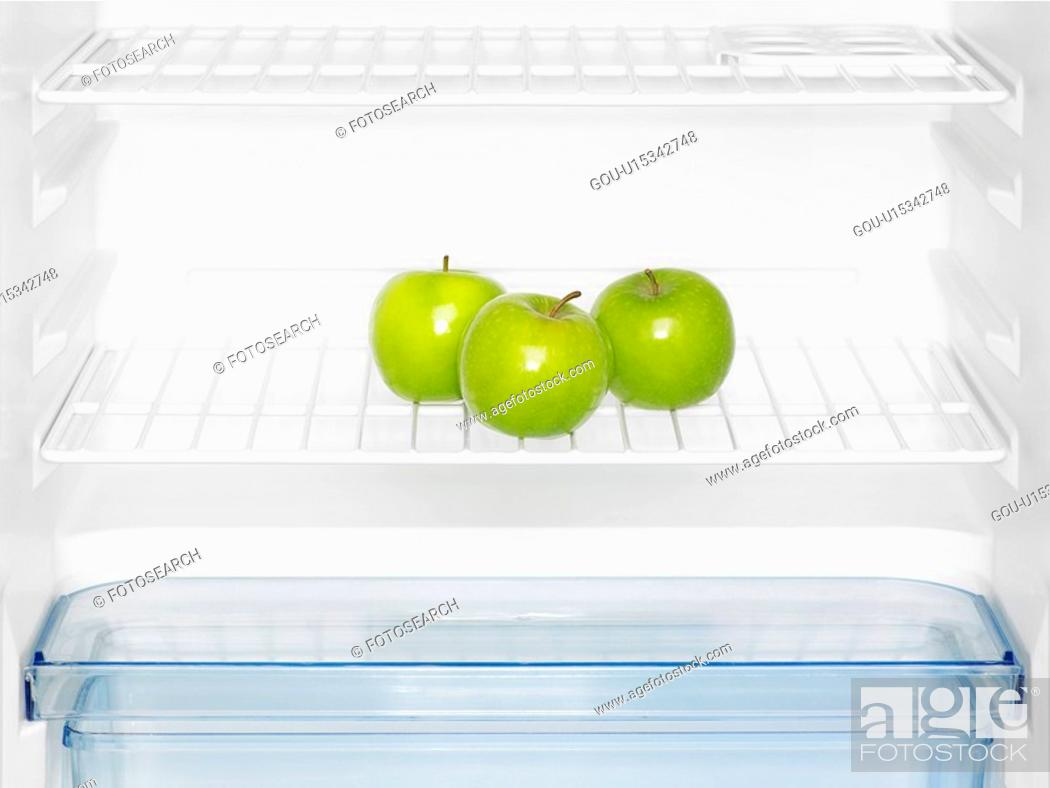 Stock Photo: Three green apples in fridge (close-up).