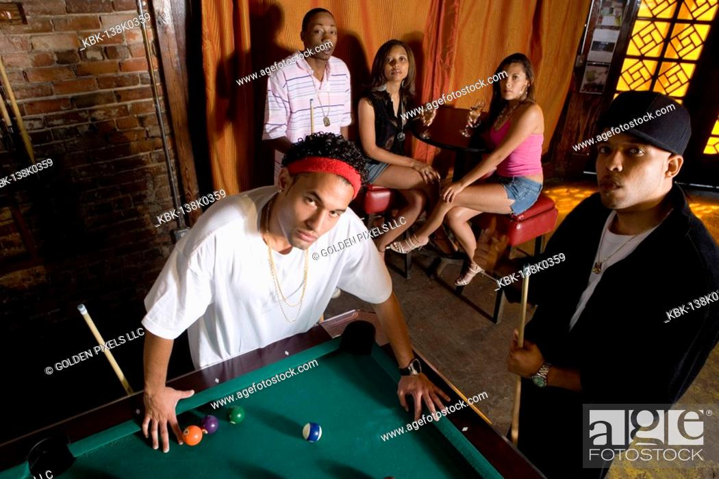 Imagen: Portrait of young men in hip-hop fashion leaning against pool table.