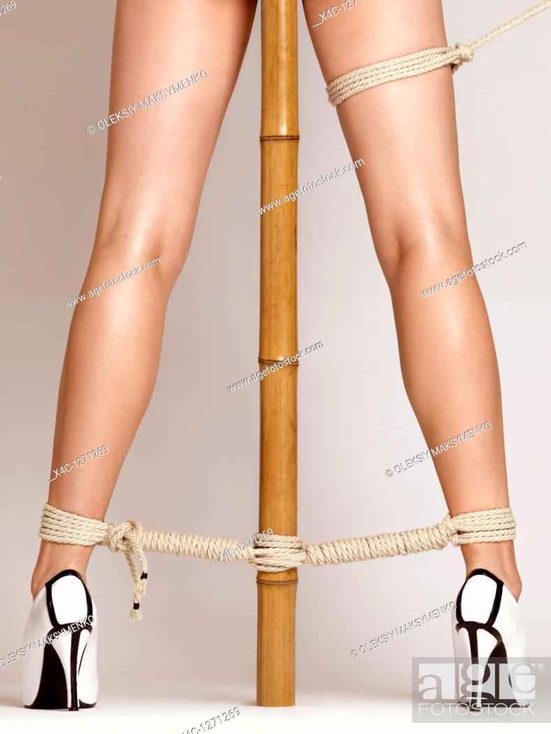 Stock Photo: Sexy woman legs tied with bondage ropes to a bamboo pole.