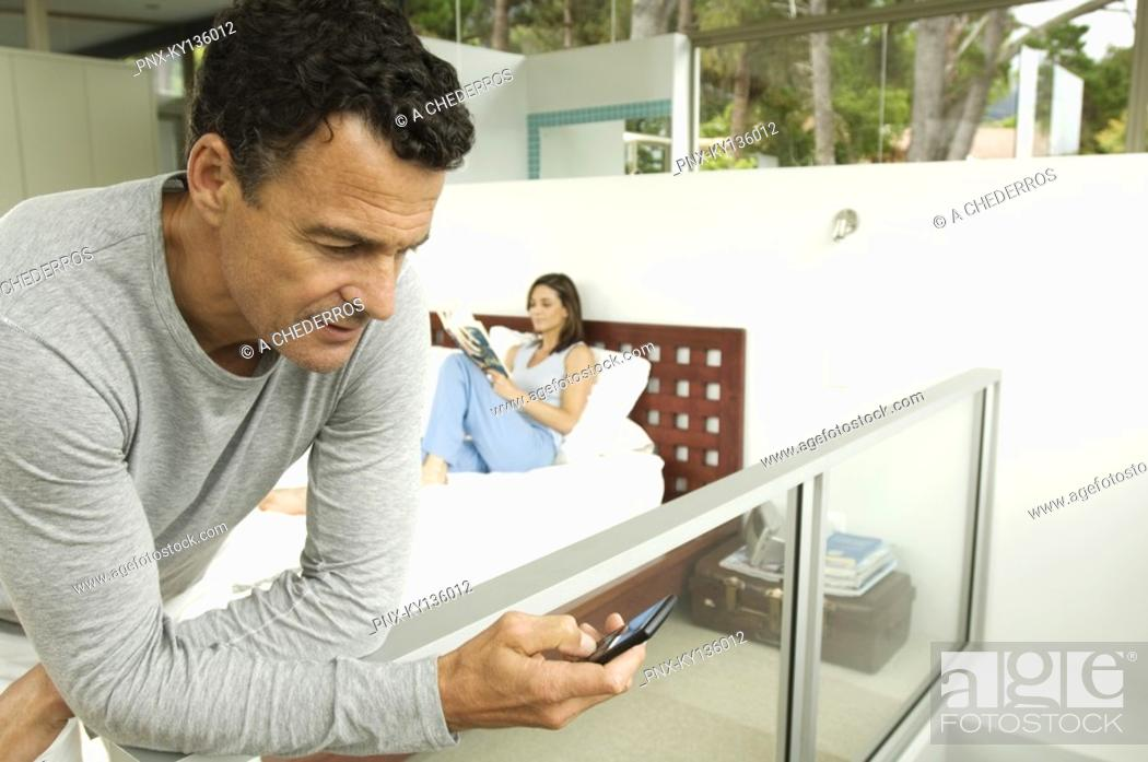 Stock Photo: Couple in bedroom, man looking his cell, woman reading magazine, indoors.