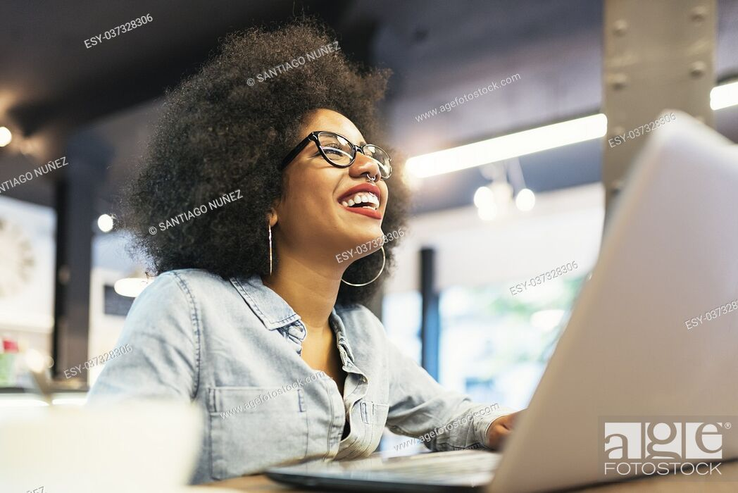 Stock Photo: Beautiful afro american woman using mobile and laptop in the coffee shop. Communication concept.