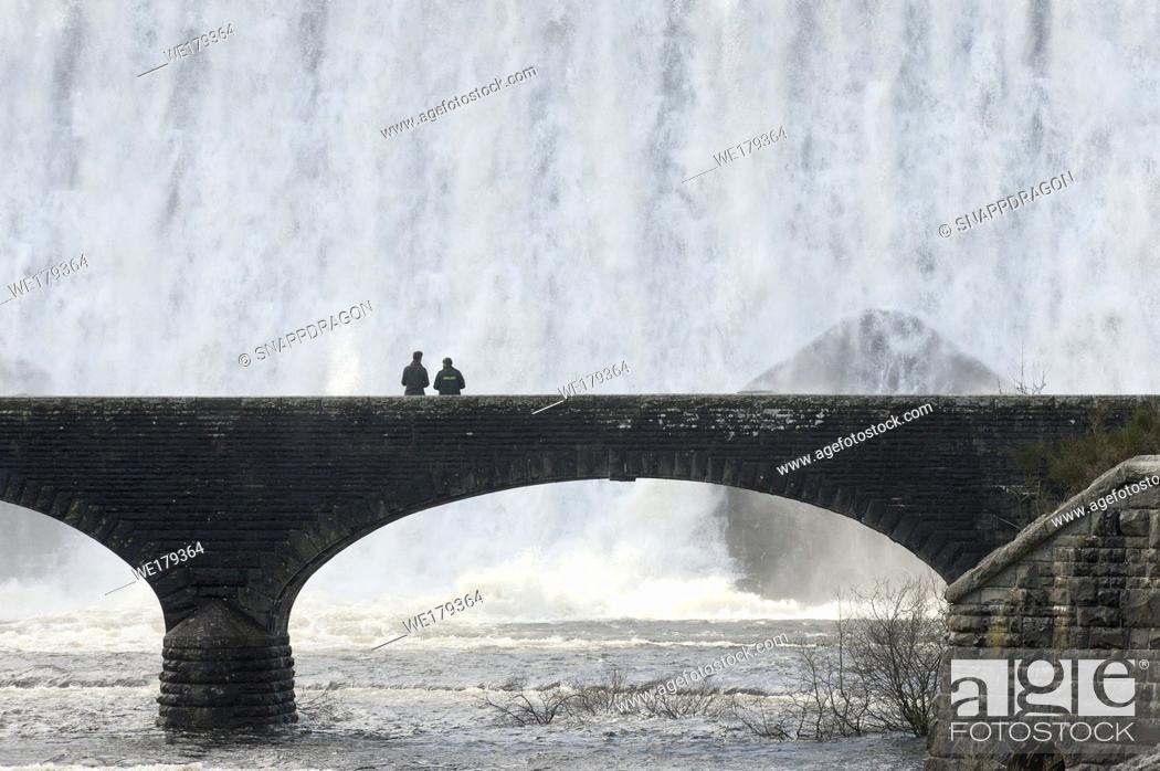 Stock Photo: Elan Valley, Powys, Wales, UK. Visitors walk across a bridge as water cascades over the Caban-coch dam, at Elan Valley village near Rhayader in Powys, Wales, UK.