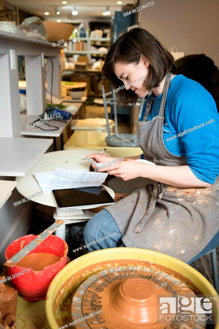 Stock Photo: Caucasian woman reading paperwork near pottery wheel.