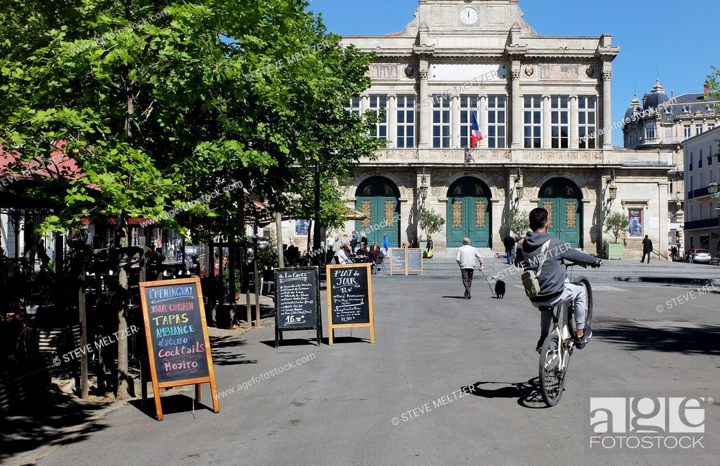 Stock Photo: Doing a wheelie in Jean Jaures, Beziers, France and the Municipal Theatre.