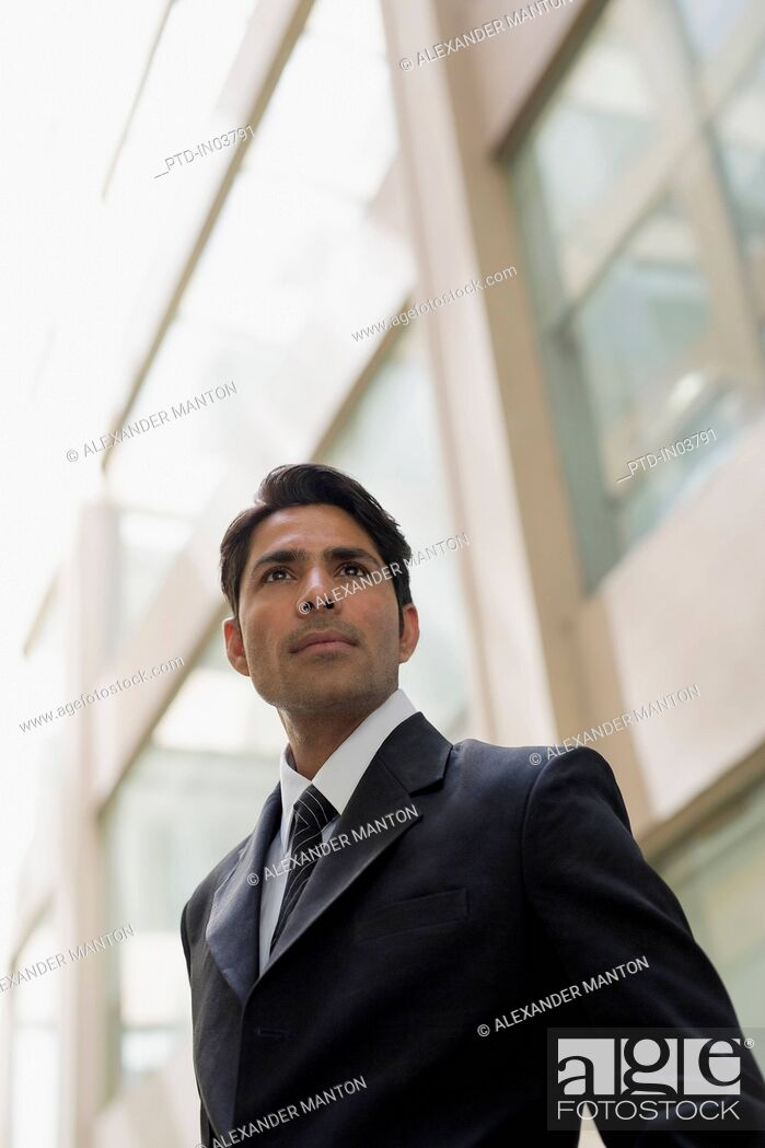 Stock Photo: Businessman outside office building looking past camera.