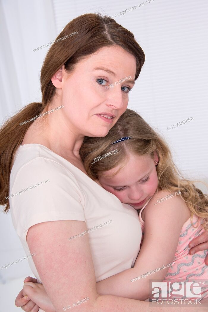 Stock Photo: Mother holding tight her little 6 year old child to comfort her.