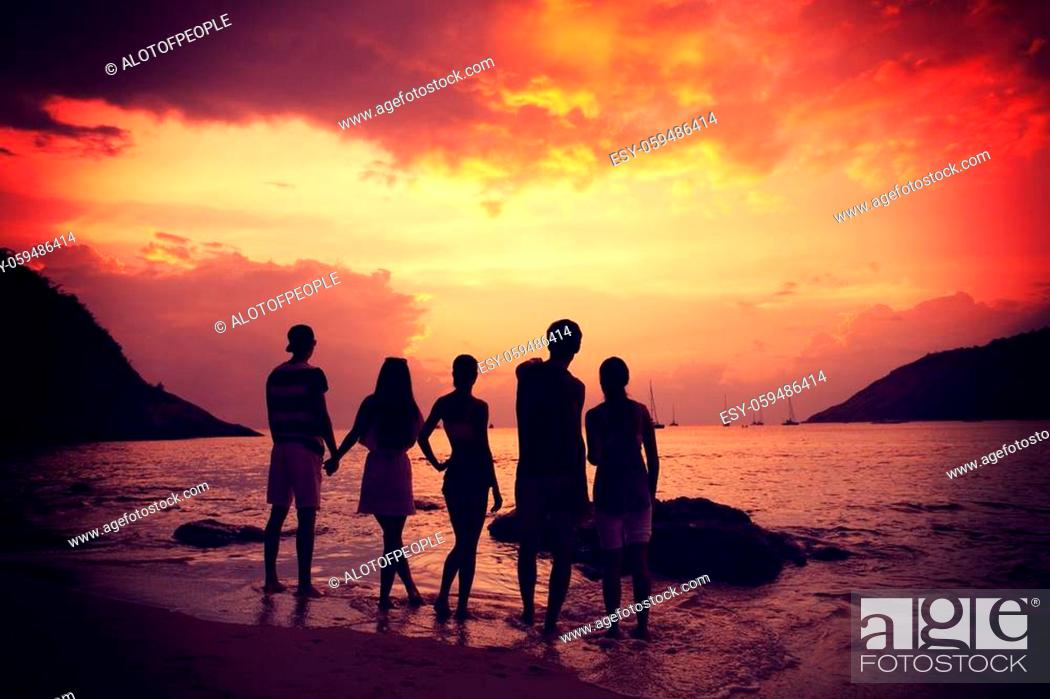 Stock Photo: Group of happy people at sea beach at sunset.