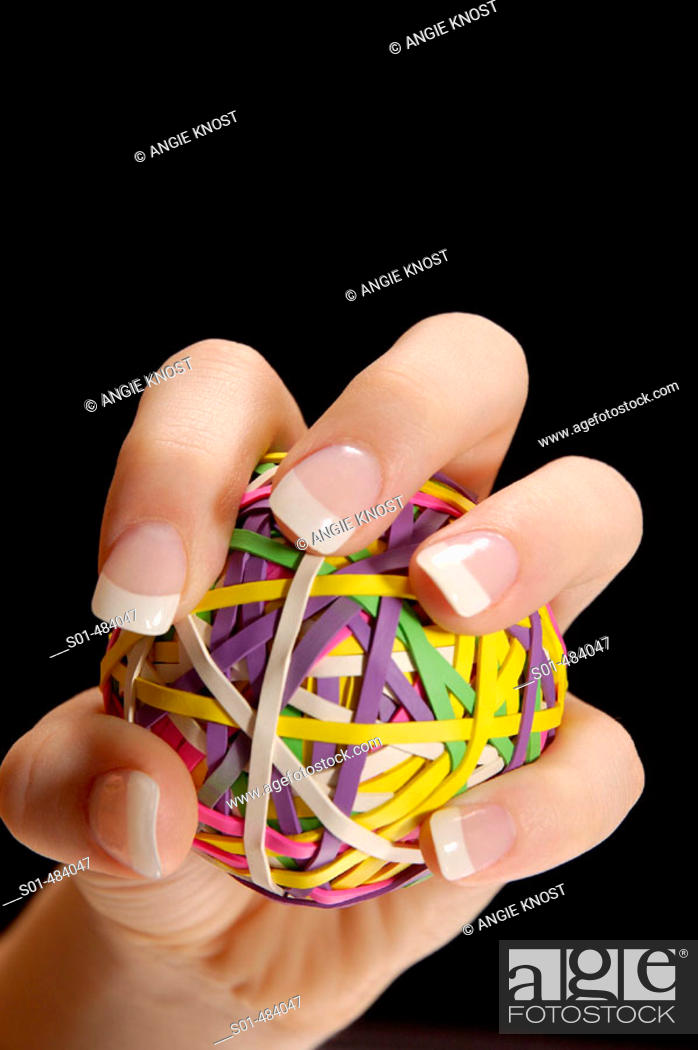 Stock Photo: Manicured female had with long fingernails, gripping a rubberband ball as if squeezing or pitching a ball.  Black backround.  Room for text/ copy.