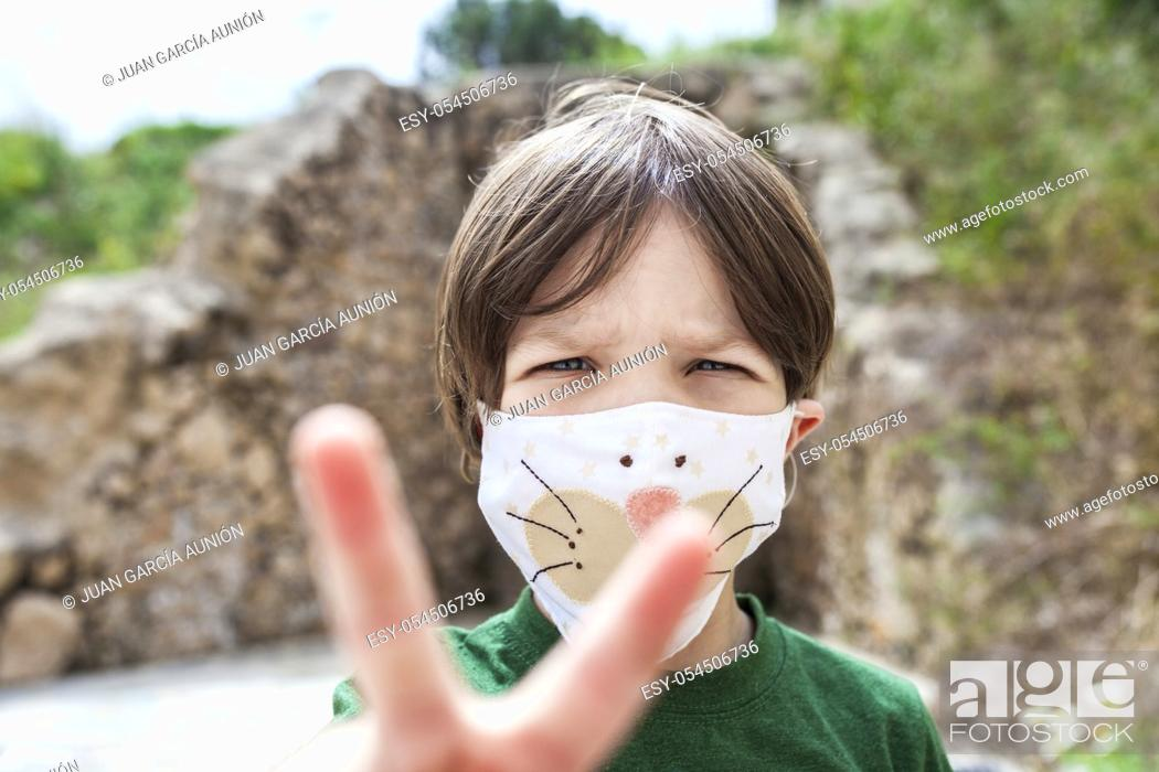 Stock Photo: Little boy holds up two fingers for victory over Covid-19 Pandemic. He is wearing face mask with children motifs.
