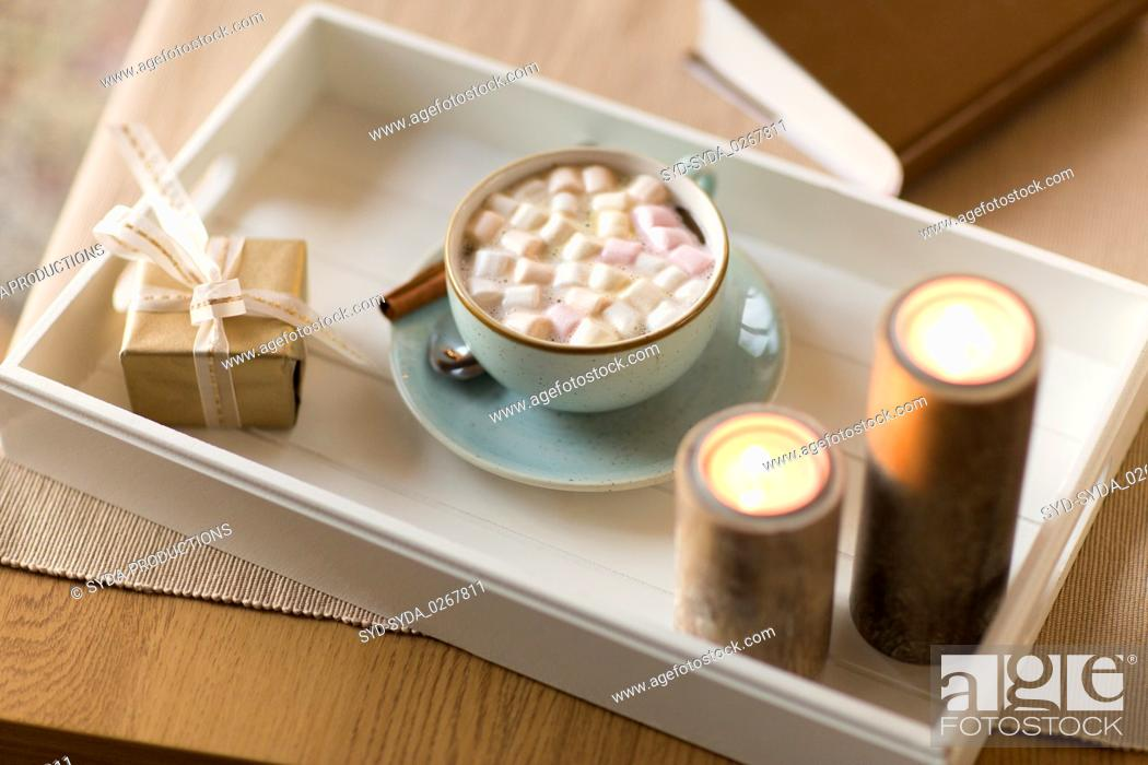 Stock Photo: hot chocolate, christmas gift and candles on table.