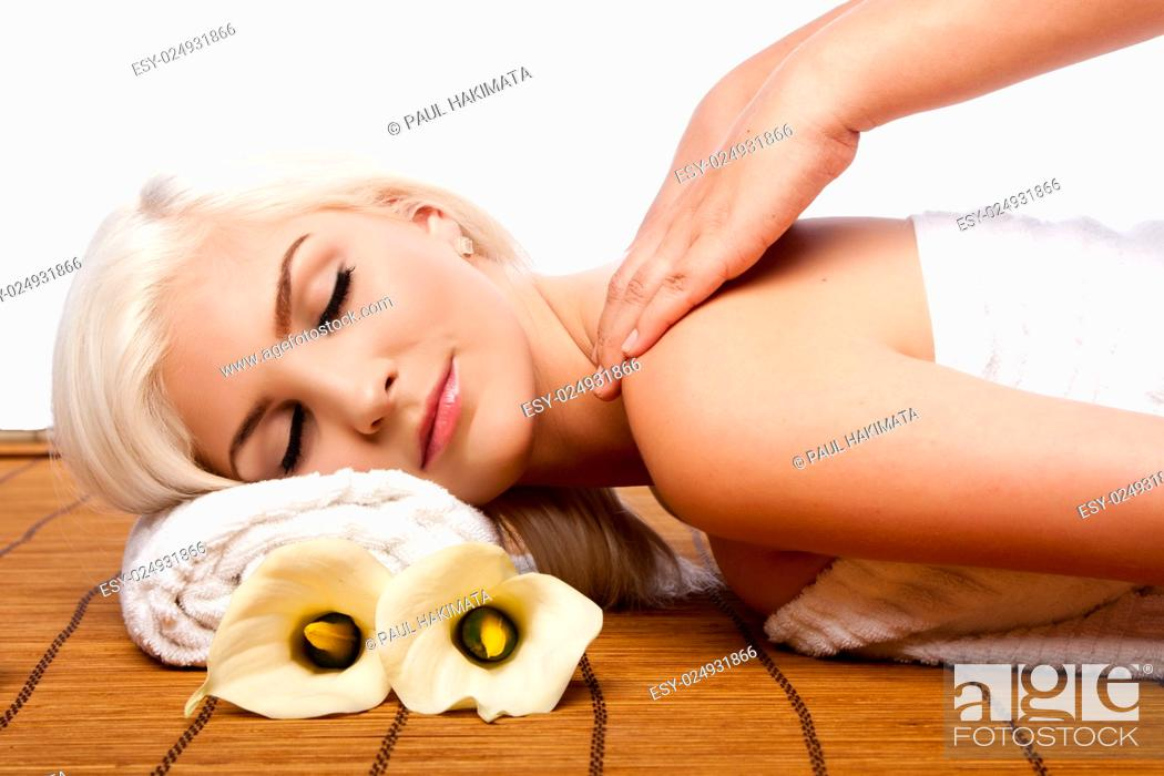 Stock Photo: Beautiful young woman relaxing at spa getting therapeutic pampering shoulder massage.