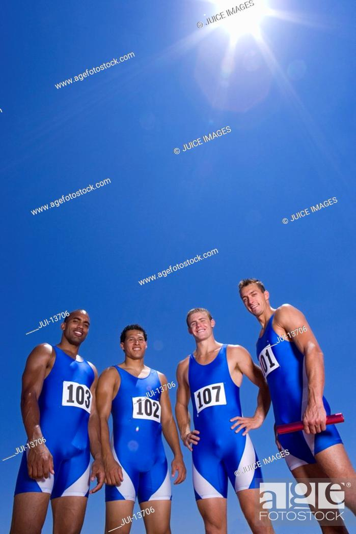 Stock Photo: Male athletes, smiling, portrait, low angle view, lens flare.