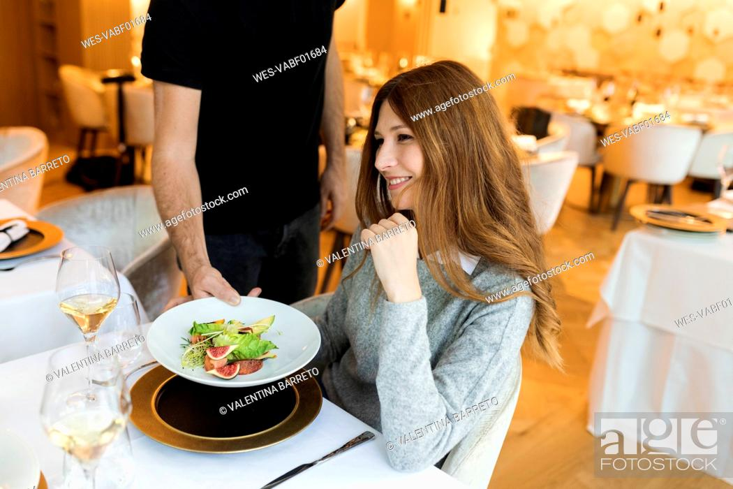 Stock Photo: Waiter serving dish for smiling woman in a restaurant.
