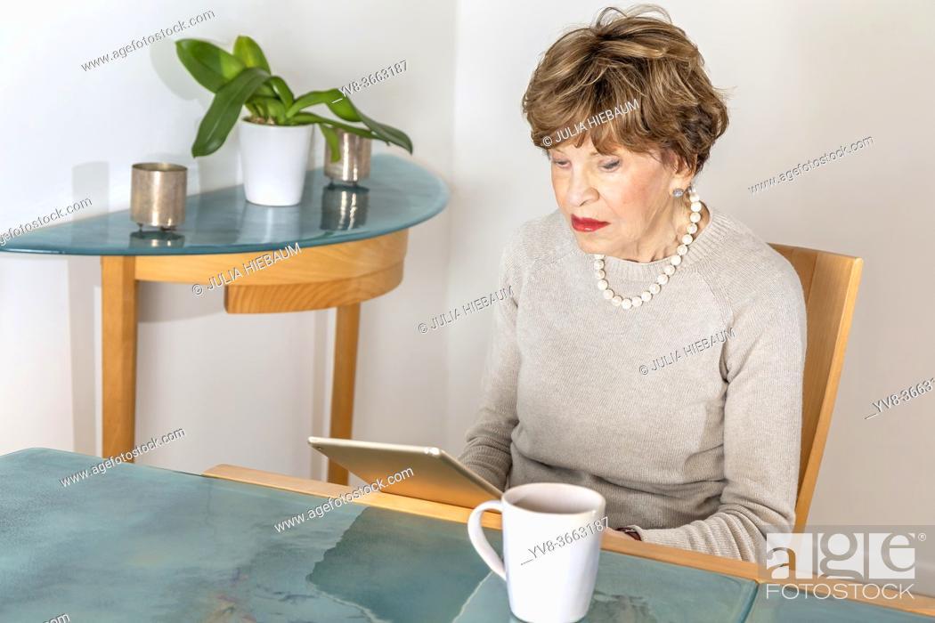 Stock Photo: EIghty year old elegant woman reading her ipad.