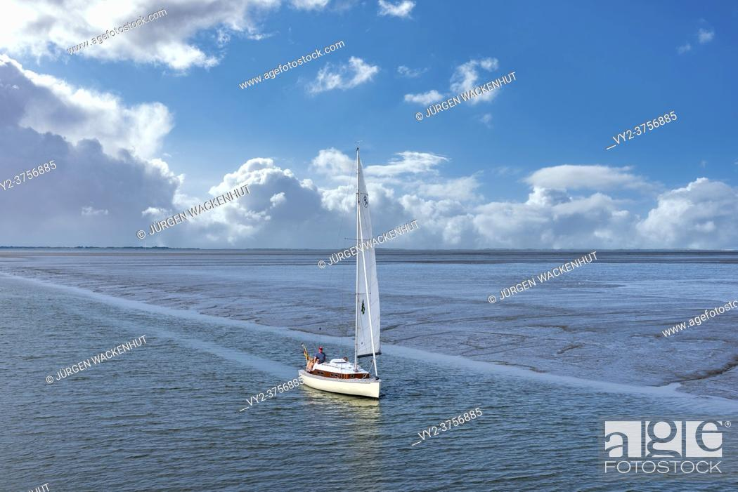 Stock Photo: Benser Aussenentief with sailing boat while entering the harbor, Bensersiel, Germany, Lower Saxony, Europe.