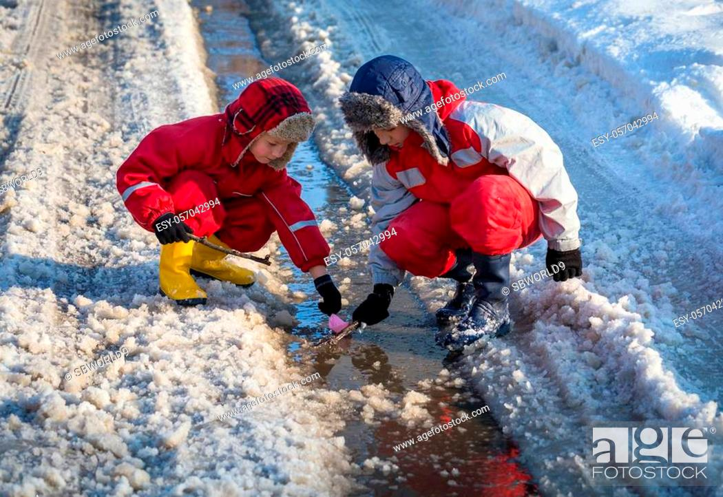 Stock Photo: Two boys in rainboots launching the paper boat at the creek with melting snow on sunny spring day, outdoors.