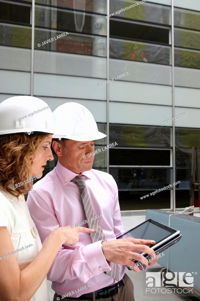 Stock Photo: Architect and client with tablet PC in construction site.