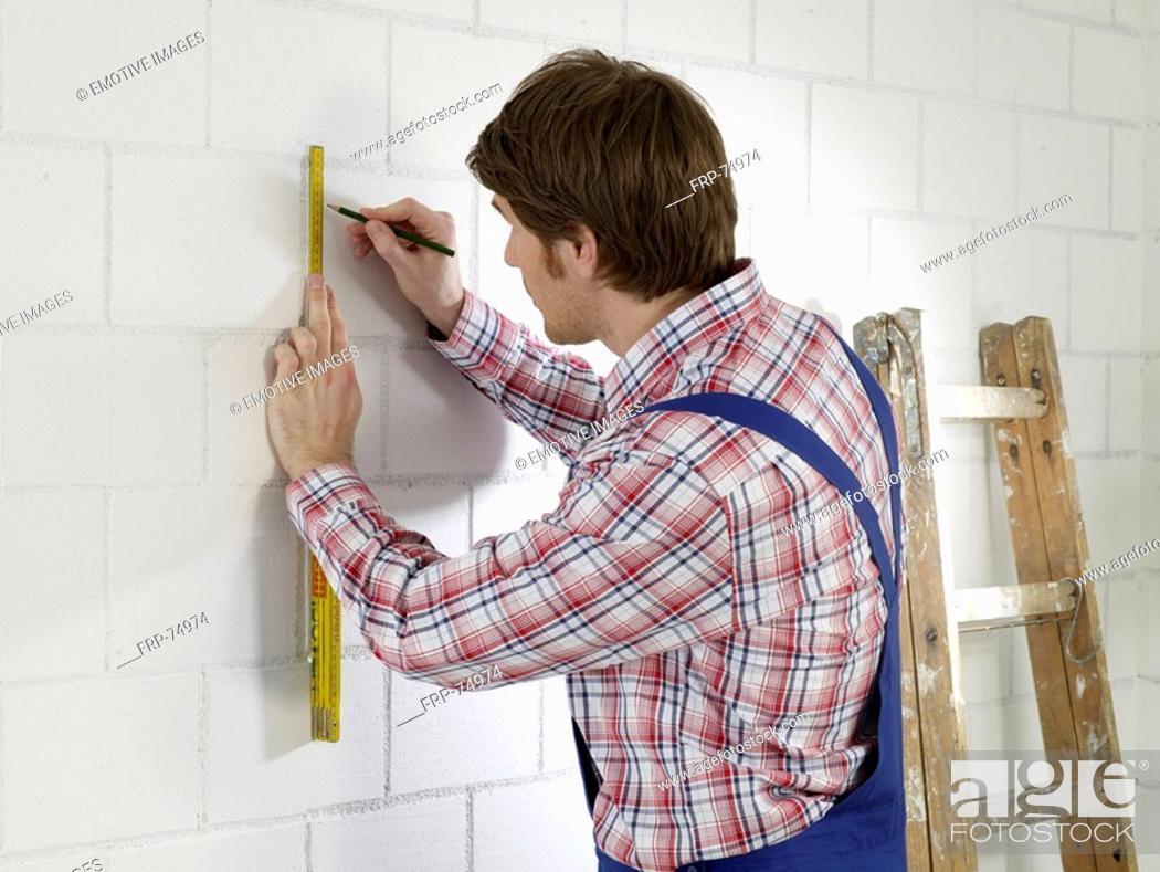 Stock Photo: Man wearing work wear is marking on wall.