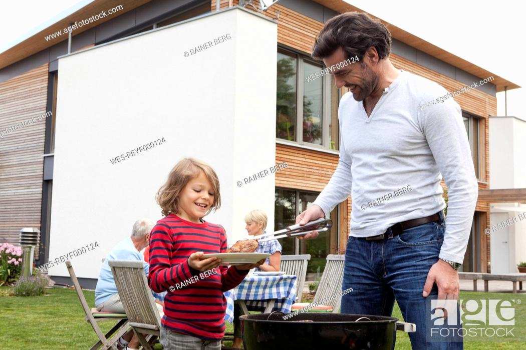 Stock Photo: Germany, Bavaria, Nuremberg, Father and son preparing food on barbecue, family sitting in background.