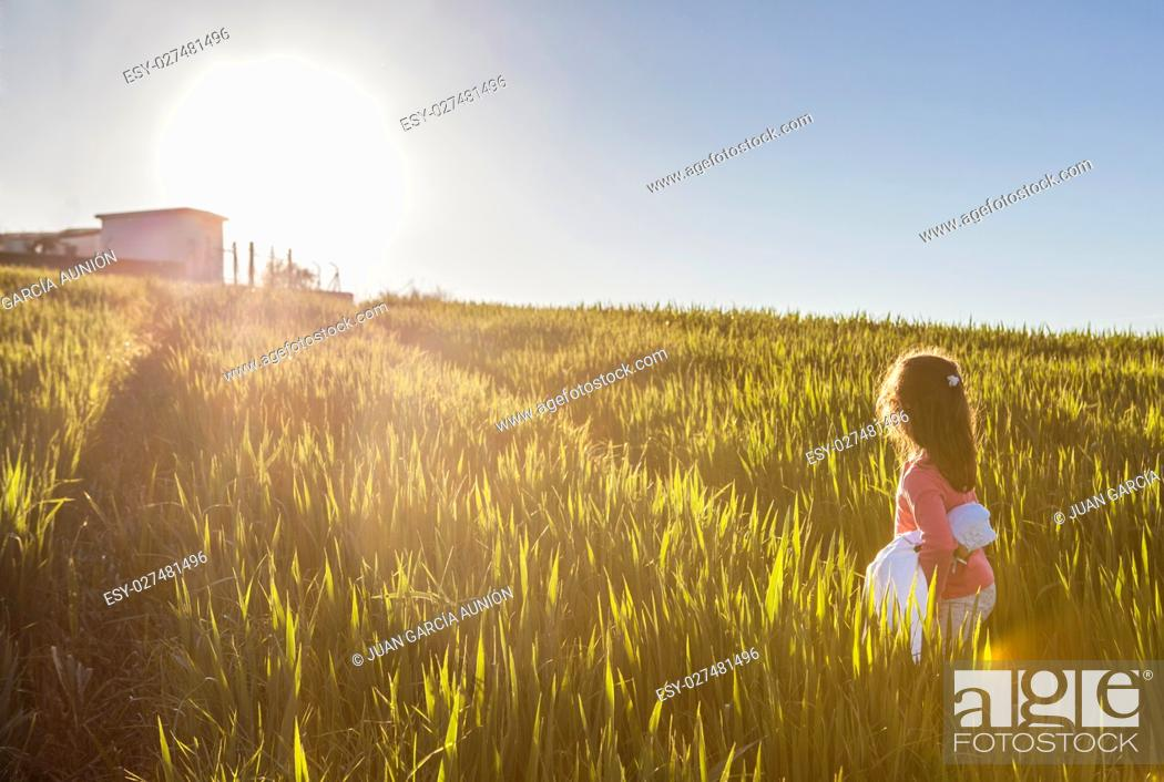 Photo de stock: Little girl and her doll walking to the sun through green cereal field. Bravery concept.