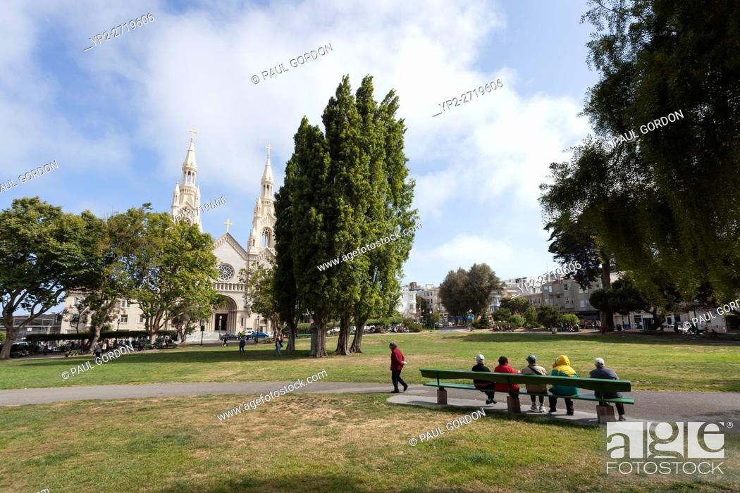 Stock Photo - San Francisco, California: Group of mature Asian friends  gathered at Washington Square, Park. In the distance is Saints Peter and  Paul Church.