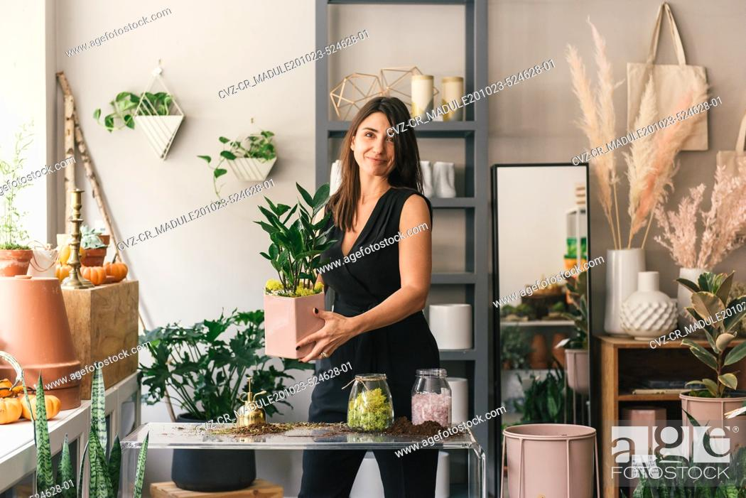 Stock Photo: Florist looking at camera in testimonial while holding fresh plant.