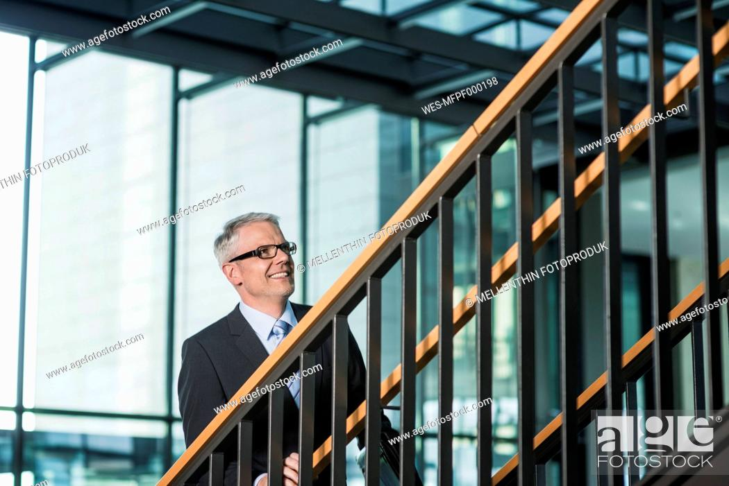 Stock Photo: Germany, Stuttgart, Businessman moving up on office staircase.