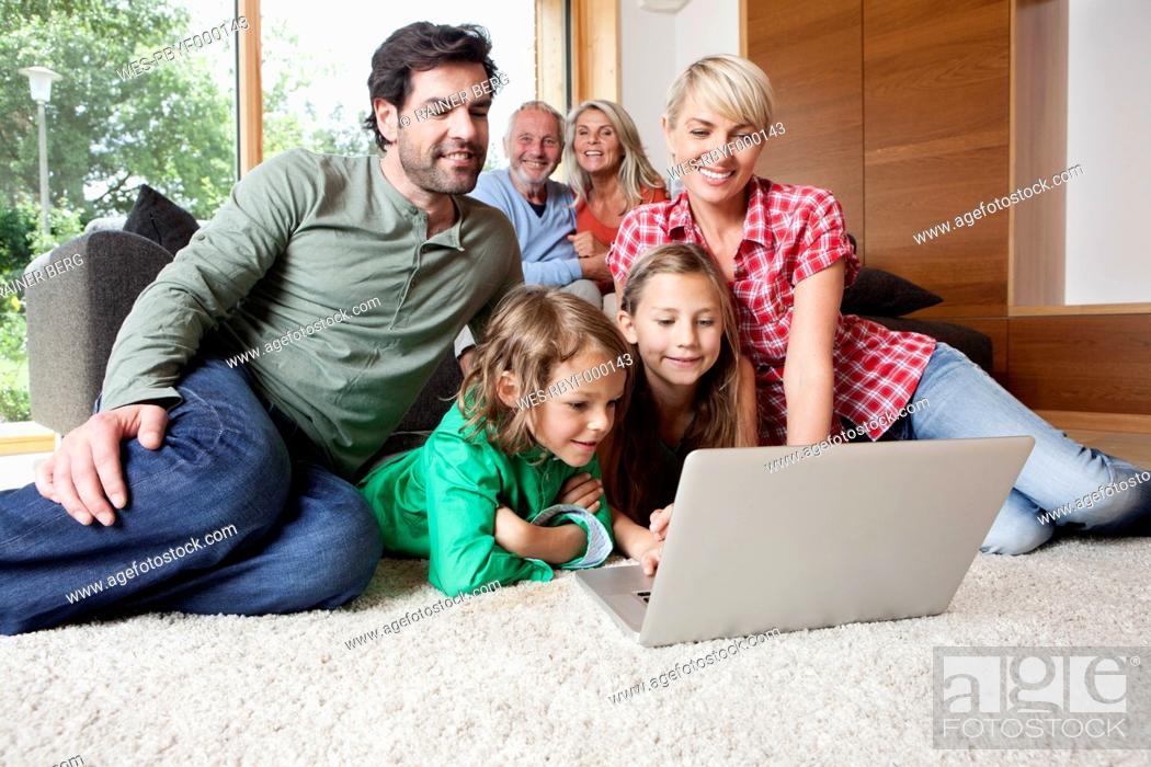 Stock Photo: Germany, Bavaria, Nuremberg, Family using laptop in living room.