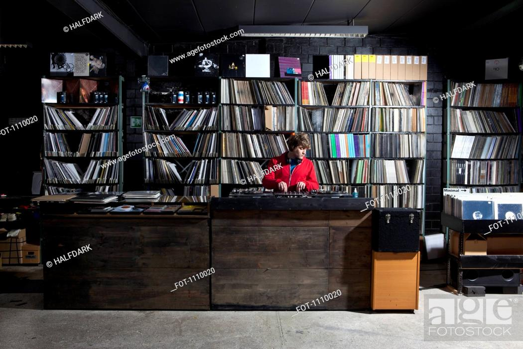 Stock Photo: A young man using decks and a sound mixer at a record store.